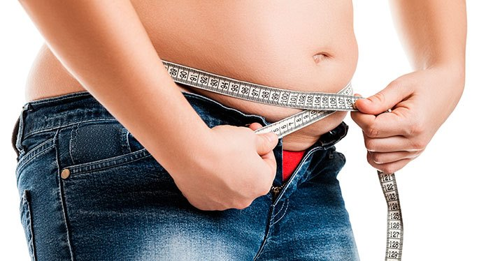 Overweight woman wearing jeans measuring her fat body belly paunch